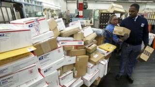 A United States Postal Service employee sorts packages in Chicago in 2012.