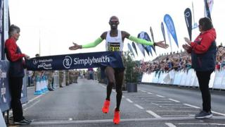 Sir Mo Farah crosses the finish line in the men's elite race