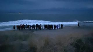 Family and friends of Deirdre McShane lay roses in the sea during a vigil