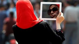 An Egyptian woman used her tablet to video protesters in Cairo's landmark Tahrir Square, 3 June 2012