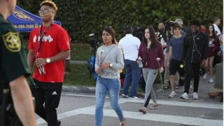 Students walk across a road holding flowers as they arrive at Marjory Stoneman Douglas high school