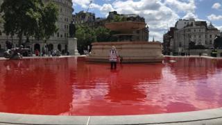 Campaigner in red Trafalgar Square fountain