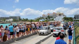 Image of people watching planes take off in Sint Maarten, taken at Maho Beach
