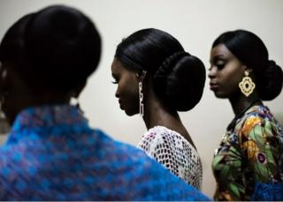 Models wait to enter the catwalk displaying creations of the Nigerian designer Nkem who is only 13 at the Africa Fashion Week in Lagos on June 3, 2017.