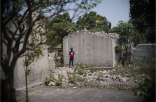A boy stands alone in the ruins of a building