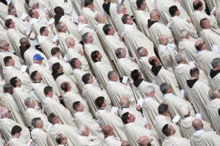 Priests are seen as Pope Francis leads a Holy Mass.