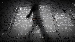 Sombra de un hombre tras códigos informáticos