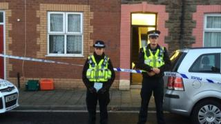 Police stand outside the property in Adeline Street