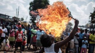 A member of Kenyan acrobat group Kibera Messenger breathes fire during a performance for filming in Kibera, Nairobi, on March 7, 2018.