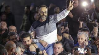 Lebanese actor Ziad Itani flashes a V for victory sign as relatives and friends carry him upon his return home in Beirut, 13 March 2018