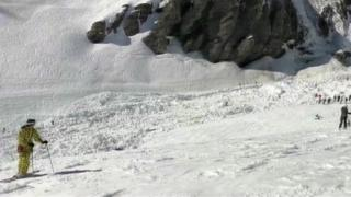 A screenshot from a video showing a large pile of dozen and skiers hit