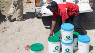 A handout picture provided on 09 October 2016 by Oxfam International shows members of an emergencies team of Oxfam delivering hygiene kits on 8th October 2016, to prevent the spread of Cholera and other diseases in the town of Camp Perrin, department Sud, Haiti
