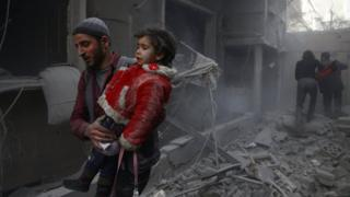 A girl is carried by a rescuer after a reported government air strike on the town of Douma, in the rebel-held Eastern Ghouta near Damascus, Syria (7 February 2018)