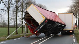 A lorry trailer is nearly blown over
