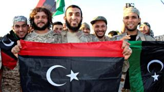 Fighters of Libyan forces allied with the U.N.-backed government hold up flags and smile