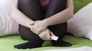 A teenage girl holding a pregnancy test