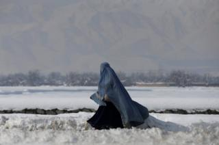An Afghan woman walks along a street covered with snow on the outskirts of Kabul, Afghanistan