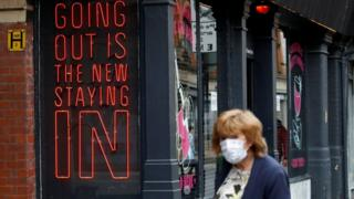 environment Woman walking past pub signage
