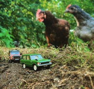 in_pictures Model red and green Land Rovers watched by chickens