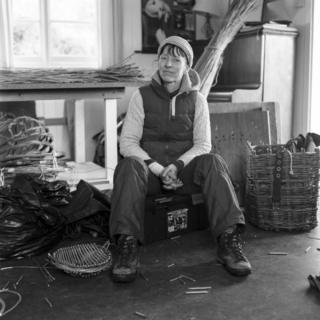 A basket weaver poses for a portrait