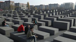 Visitors sit while visiting the Holocaust Memorial in Berlin