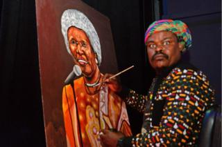 Rasta, whose real name is Lebani Sirenje, sit at an easel painting a large canvas with a brush.