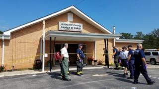 The Burnette Chapel Church of Christ - a low brick building with white eaves, surrounded by emergency workers and encircled in police tape