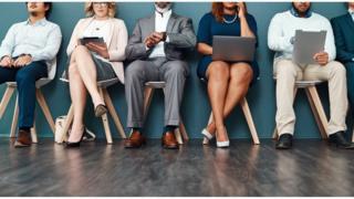 Pessoas sentadas em diferentes cadeiras trabalhando