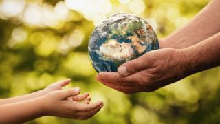 Un adulto pasando una esfera que representa la Tierra a las anos de un niño o niña
