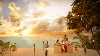 Couple having dinner on sandy beach at sunset