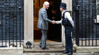 Bill Clinton shaking hands with a police officer outside 10 Downing St