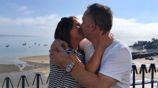 Emma Cornick and Neil Brierley kissing at Tenby beach after getting engaged