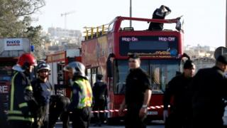 A forensics investigator stands on an open top, double-decker sightseeing bus in Zurrieq