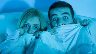 Una pareja aterrada viendo una película