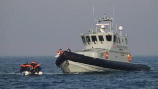 Border Force officers aboard HMC Hunter speak to group of people, thought to be migrants