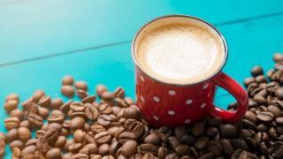 كوب من القهوة بجوار حبوب البن المحمصة