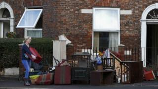 A woman brings her flood-hit furniture on to a Carlisle street