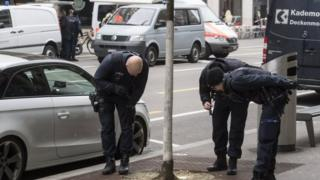 Police teams check the area following the shooting incident in Zurich