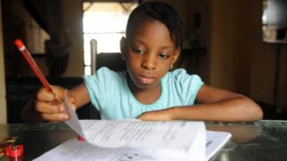 USE Omoze Ogwogho, 7, a pupil of the Christower International Schools, one of Nigeria's private schools, does her homework on June 8, 2013 at home in the southwestern city of Ibafo, Ogun State.