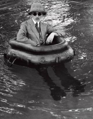 A man in a suit sits in a rubber ring in open water