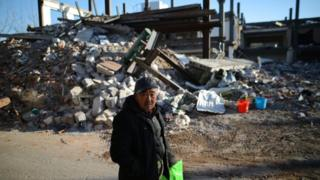 A local resident walks near the debris of a building demolished by local officials during a citywide fire safety inspection in November 2017, in Beijing