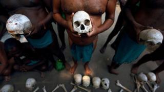 A row of men hold skulls.