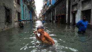 Hombre avanza por una calle inundada de La Habana tras el paso del huracán Irma.