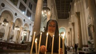 A nun lights a candle as Catholics attend the Christmas eve mass at Saint Joseph Catholic Church in Cairo,
