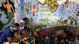 Awọn olujọsin n gbadura ni waju ojubọ kan ni eti odo Salvador, nipinlẹ Bahia, l'orilẹede Brazil nigba ọdun Yemanja (Iyemọja), oriṣa odo lati ẹsin abalaye Yoruba to jẹ ọkan lara awọn oriṣa to gbajumọ ju ninu aṣa awọn adulawọ nilẹ Brazil.