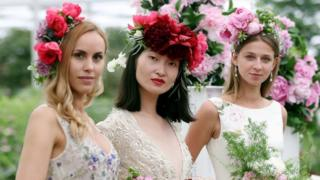 Three models wearing bridal designs by Alan Hannah hold bouquets of peonies in the Great Pavillion during the press day for this year's RHS Chelsea Flower Show