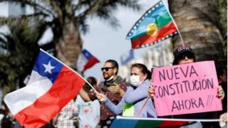 Manifestantes sostienen banderas y carteles