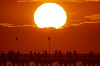 The sun sets behind a cloud as people cool off with a walk along an ocean pier in Oceanside, California, US on 5 July 2018