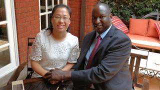 Xu Jing and Henry Rotich hold hands as they sit at a table
