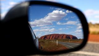 Australia's famed outback landmark, Uluru, pictured in a car's rear view mirror
